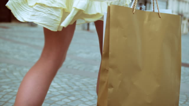 slo mo female with shopping bag walking on the street - paper bag stock videos & royalty-free footage