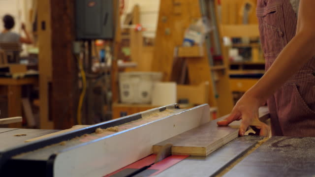 vídeos de stock, filmes e b-roll de ms female woodworker cutting piece of plywood on table saw while working in cabinet shop - serra elétrica