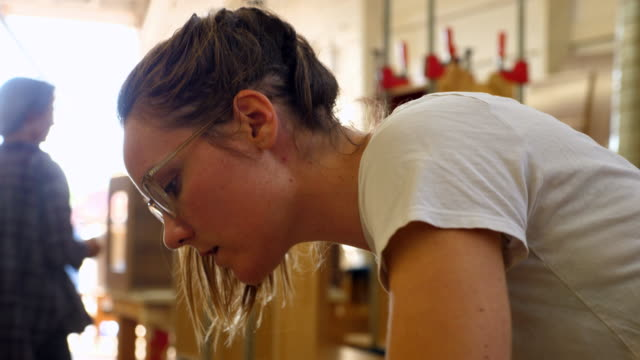 ms female woodworker sanding piece of wood for project in cabinet shop - craftsperson stock videos & royalty-free footage