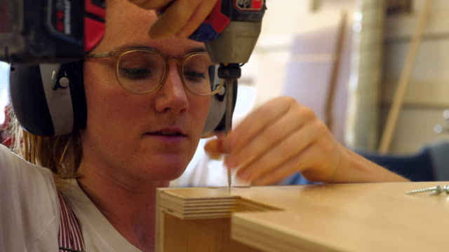 MS Female woodworker screwing together cabinet in woodshop