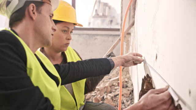Female worker and construction manager discussing the measurement of the wall