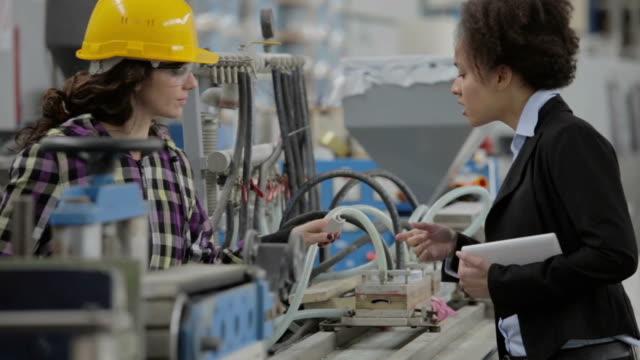 vidéos et rushes de femme travailleur inspecteur qualit et femmes parler - chaîne de production