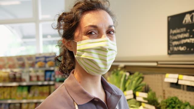lavoratrice al negozio di alimentari durante la pandemia di covid-19 - mercante video stock e b–roll