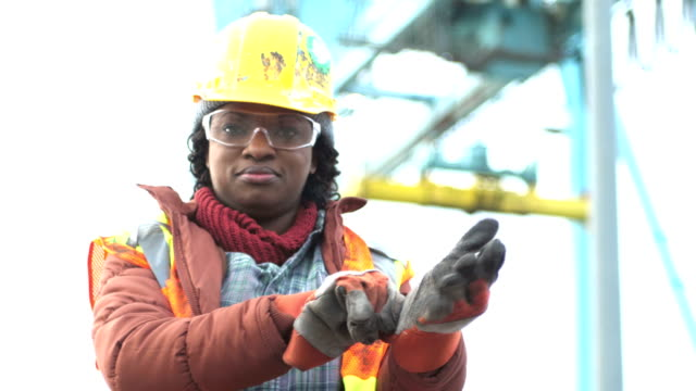 Female worker at shipping port puts on work gloves