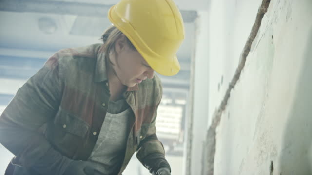 female worker chipping away the wall with a jackhammer - wall building feature stock videos & royalty-free footage