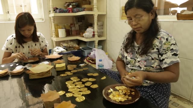 female worker cuts strips of gold leaf and puts them between sheets of bamboo paper to be hammered at the king galon gold leaf workshop in mandalay,... - gold leaf stock videos & royalty-free footage