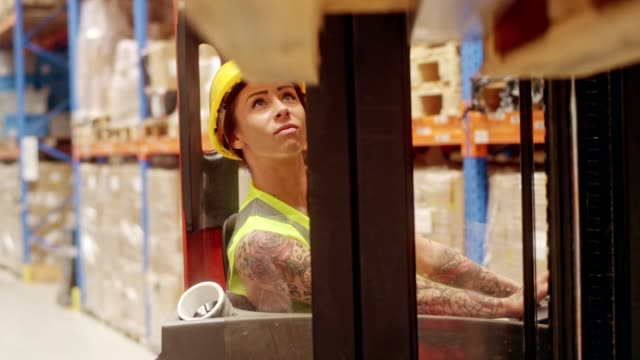 female worker driving on a forklift. warehouse - forklift stock videos & royalty-free footage