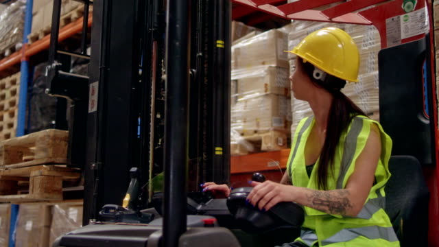 female worker driving on a forklift. warehouse - forklift truck stock videos and b-roll footage