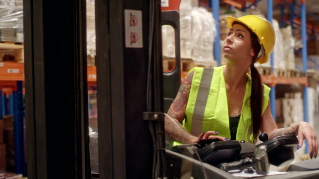 female worker driving on a forklift. warehouse - equality stock videos & royalty-free footage