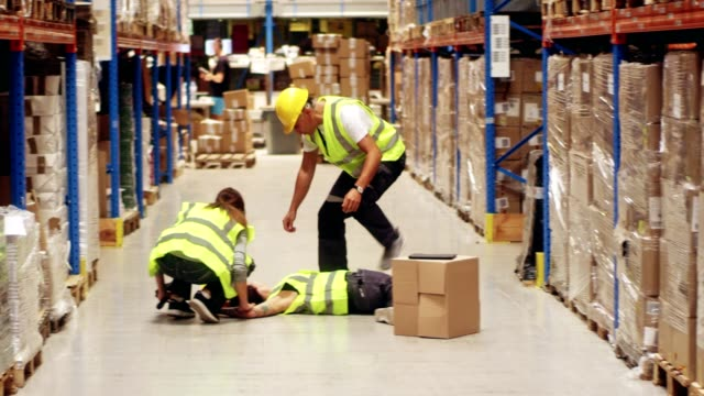 female worker falling down in warehouse - safety stock videos & royalty-free footage