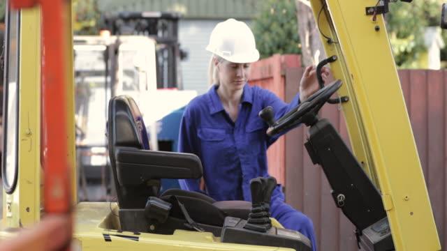 フォーク リフトに入る女性労働者 - white collar worker点の映像素材/bロール