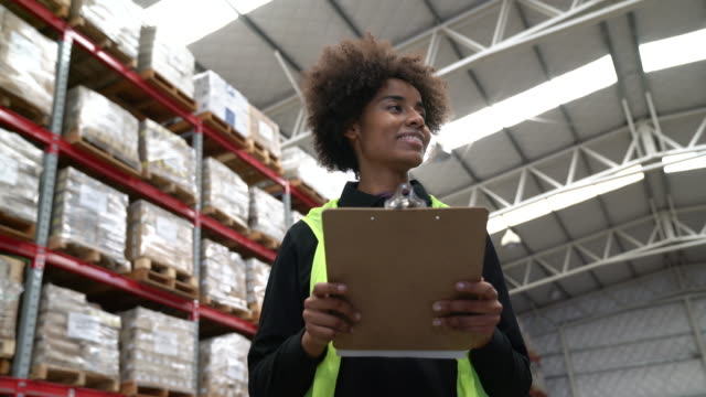 female worker holding clipboard in warehouse - frizzy hair stock videos and b-roll footage