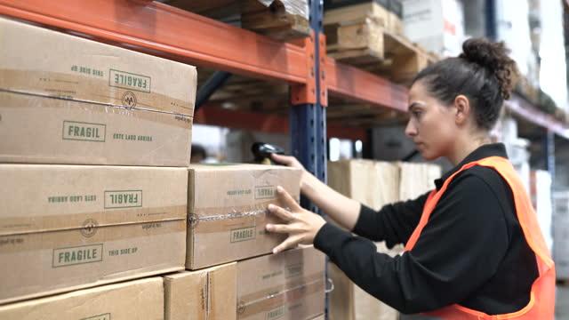vidéos et rushes de travailleuse dans des boîtes de balayage uniformes sur un étagère d'entrepôt - marchandise