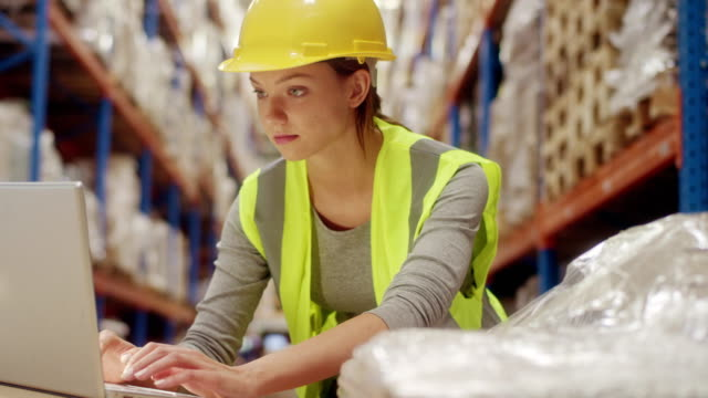 Female worker in warehouse. Using laptop