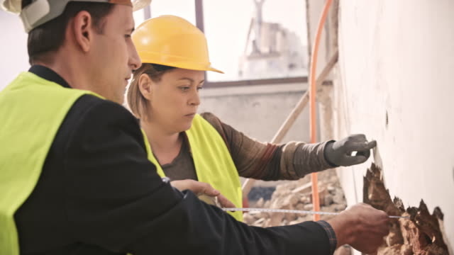 female worker measuring the wall for the corrugated tubes while the construction manager is talking to her - elmetto da cantiere video stock e b–roll
