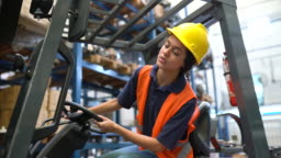 Female worker operating forklift in warehouse