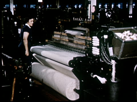 vidéos et rushes de ms, female worker overseeing factory loom weaving cotton fabric - usine textile