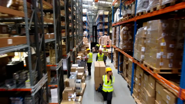 female worker using pallet jack. forklift worker in background. drone point of view - distribution warehouse stock videos & royalty-free footage