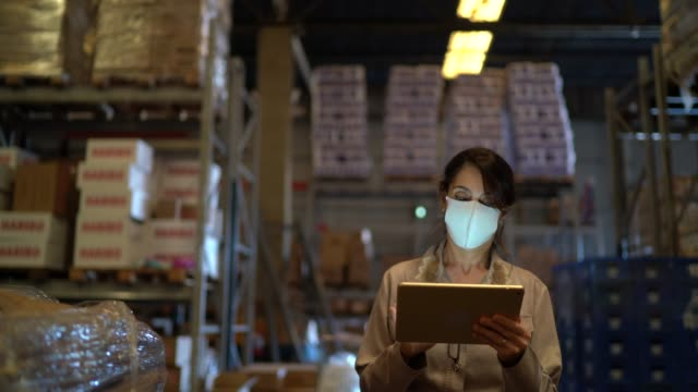 female worker walking and using digital tablet at warehouse - with face mask - shipping stock videos & royalty-free footage