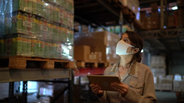 vídeos de stock e filmes b-roll de female worker walking and using digital tablet at warehouse - with face mask - fábrica