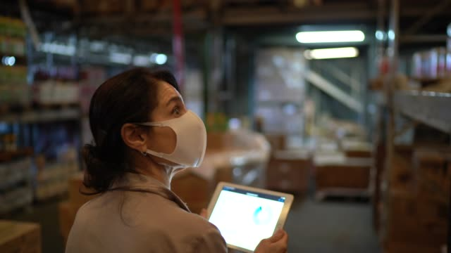 female worker walking and using digital tablet at warehouse - with face mask - distribution warehouse stock videos & royalty-free footage