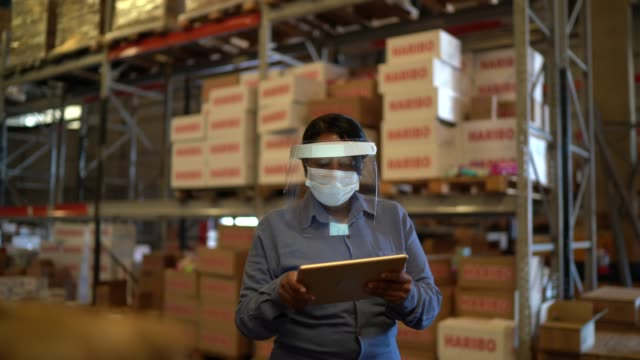 vídeos de stock e filmes b-roll de female worker walking and using digital tablet at warehouse - with face mask - e commerce