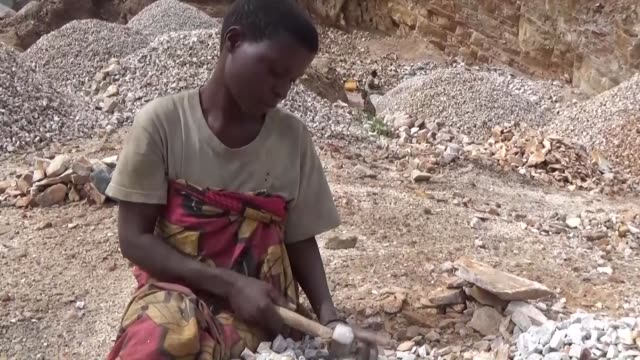 female workers break and load stones at a quarry in isare district of bujumbra, burundi on november 07, 2015. many women work at quarries for... - mining点の映像素材/bロール