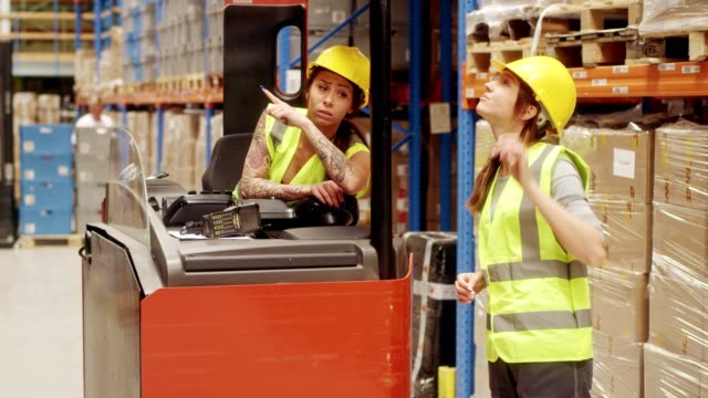 female workers driving on a forklift and looking for stock. teamwork - forklift truck stock videos and b-roll footage