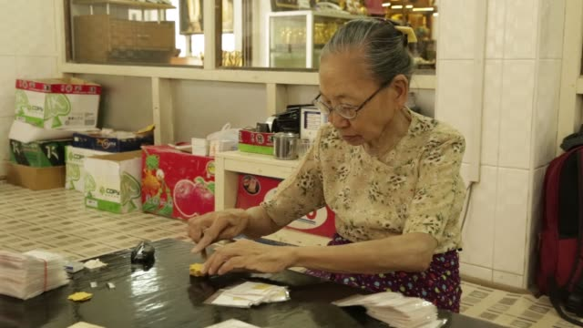 female workers package single sheets of gold leaf at the king galon gold leaf workshop in mandalay, myanmar, on sunday, june 11 a female worker packs... - gold leaf stock videos & royalty-free footage