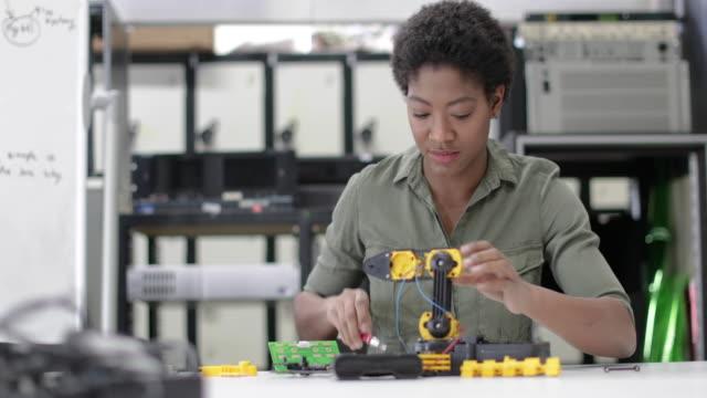 female working on robotics - tecnico video stock e b–roll