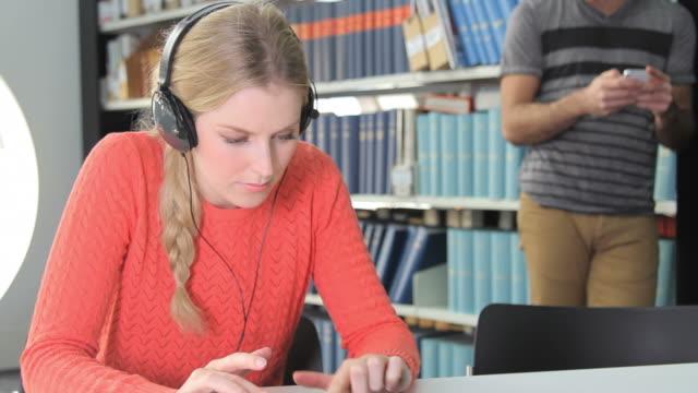 femmina lavorando su ipad e ascoltare musica - cuffia attrezzatura per la musica video stock e b–roll
