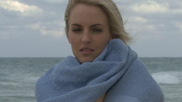 stockvideo's en b-roll-footage met female wrapping a towel around her on a beach - in een handdoek gewikkeld