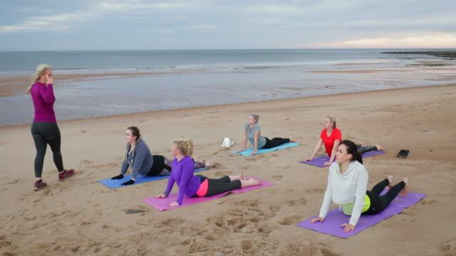 female yoga beach class - recreational pursuit stock videos & royalty-free footage