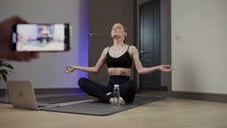Female yoga instructor shoots a video lesson, drinks water and meditates