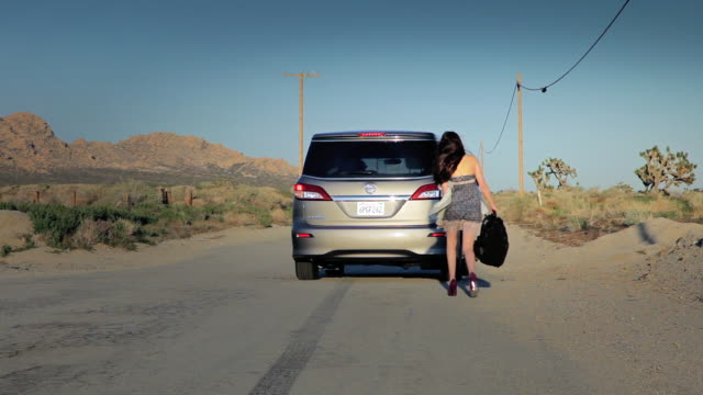 ws female young tramper grabs stuff and jumping into car / palmdale, ca, united states      - palmdale stock videos and b-roll footage