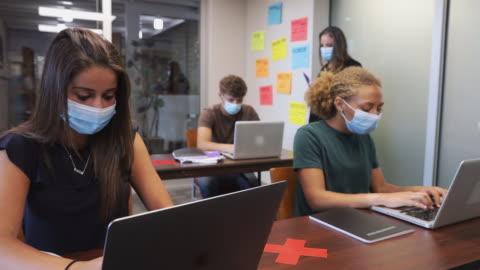 vídeos y material grabado en eventos de stock de mujeres y estudiantes de secundaria masculinas y profesora en el aula usando máscaras 4k video - education