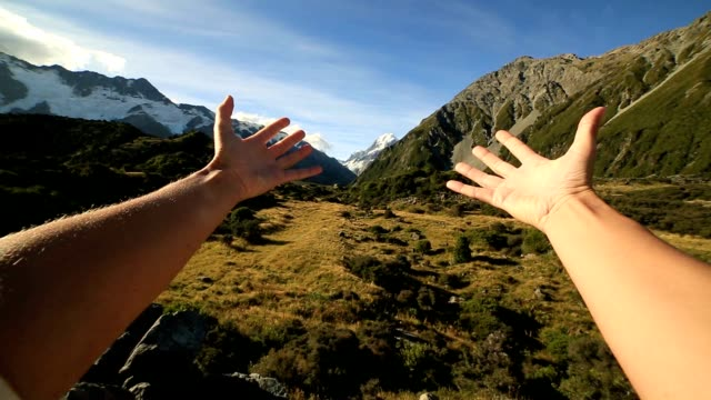 Female's arms stretches towards the Mount Cook