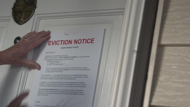 vídeos y material grabado en eventos de stock de manos caucásicas de mujer colgando un aviso de desalojo de papel en la puerta principal de una casa de alquiler en un vecindario suburbano residencial - señal de información