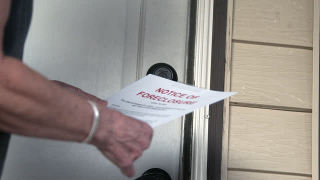 female's caucasian hands hanging a paper foreclosure notice on the front door of a home - western script stock videos & royalty-free footage
