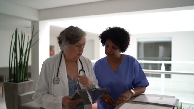 vídeos de stock, filmes e b-roll de médica e enfermeira do sexo feminino falando em secretário de hospital e caminhando - secretária