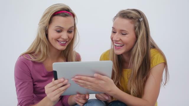 vídeos y material grabado en eventos de stock de females friends using an ebook - cinta de cabeza