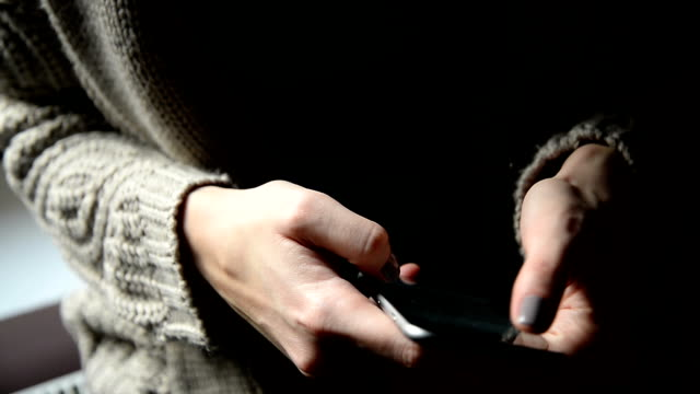 Female's hands using phone. Close up
