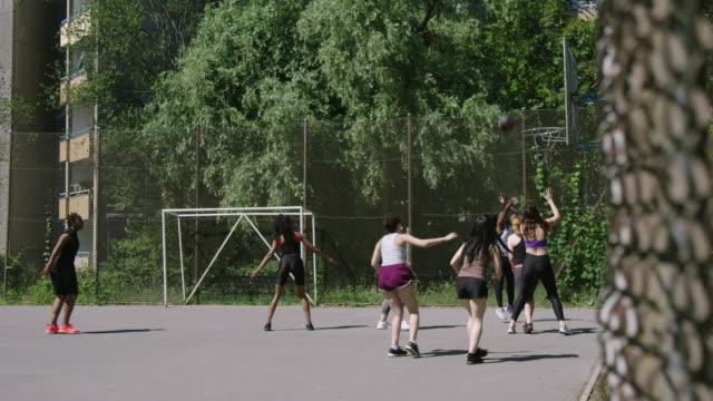 vidéos et rushes de femmes jouant le streetball sur le terrain de sports - streetball