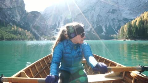 females rowing wooden small boat on alpine lake at sunrse - europäischer abstammung stock-videos und b-roll-filmmaterial