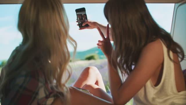 vidéos et rushes de femelles prenant le selfie pendant le camping dans le fourgon - camping