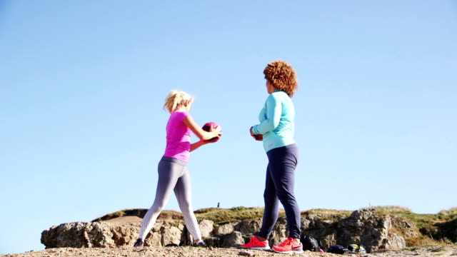 Females Training with a Medicine Ball in the Open Air