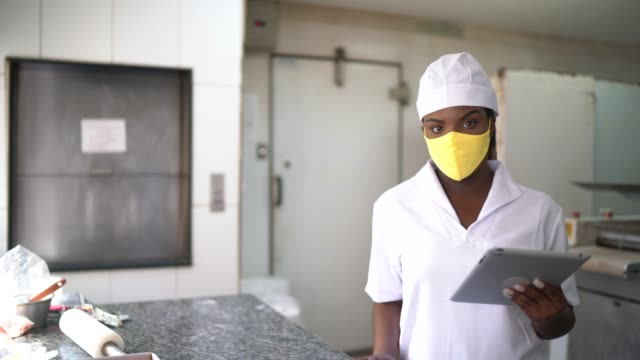 fenale chef using digital tablet in a commercial kitchen with face mask - quality control stock videos & royalty-free footage