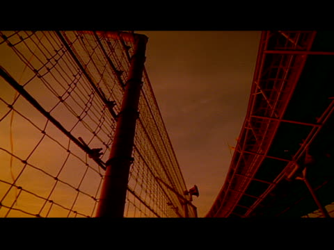a fence and race track are silhouetted by an orange sky - sportstrecke stock-videos und b-roll-filmmaterial
