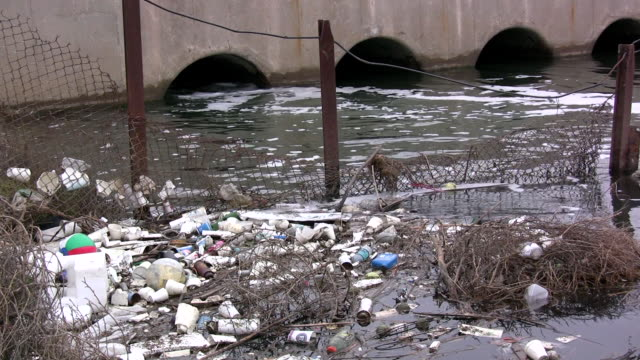 ws fence blocking garbage from flowing into sewer drain / huntington beach, california, usa - polystyrene stock videos & royalty-free footage