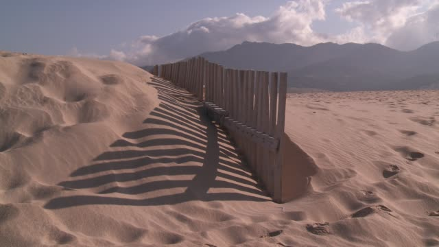 A fence casts a shadow on the sand dunes in Tarifa, Spain.